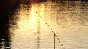 A beautiful lake with a fixed spinning at a splendid sunset. A gorgeous view of a nice lake in the dusk of sunset with one spinnings fixed to catch fish. It stock footage