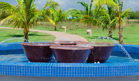 Gorgeous view of outdoor decorated pool with big marble bowels inside against tropical garden background Stock Photo