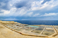 Gorgeous view from salt pans Gozo, Malta with cloudy sky. Stock Photos