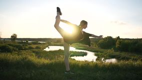 Flexible girl bending forward and doing a front split at a pond at windy sunset in slo-mo. Gorgeous view of a slender fair-haired girl in shorts bending forward stock video