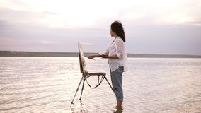 Gorgeous view of a young curly brunette standing in the water with easel and draing her the surrounding landscape stock footage