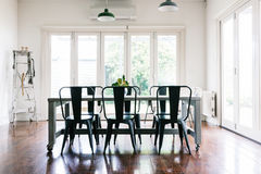 Gorgeous vintage styled dining room with bifold doors. Gorgeous vintage styled light bright dining room with bifold doors Royalty Free Stock Image