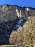 Gorgeous waterfall at famous Lauterbrunnen valley and Swiss Alps with sunlight reflection in winter season stock photo