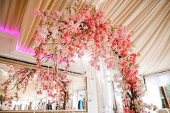 Gorgeous wedding arch decorated with beautiful pink flowers. Gorgeous wedding arch decorated with a lot of bright and beautiful pink flowers on the white indoors Stock Image