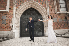 Gorgeous wedding couple, bride, groom posing near old gate building Royalty Free Stock Photos