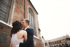 Gorgeous wedding couple, bride, groom posing near old gate building Stock Photos