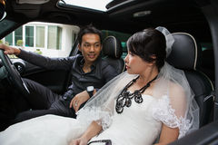 Gorgeous wedding couple in car Royalty Free Stock Images