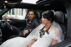 Gorgeous wedding couple in car Stock Photos
