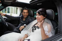 Gorgeous wedding couple in car Royalty Free Stock Photos