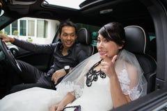 Gorgeous wedding couple in car Royalty Free Stock Photos