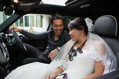 Gorgeous wedding couple in car Stock Images