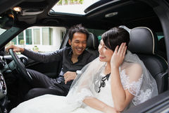 Gorgeous wedding couple in car Stock Image
