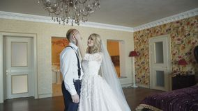 Gorgeous wedding couple kisses with smile in luxurious bedroom stock video footage