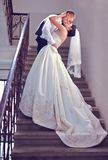 Gorgeous wedding couple kisses on stairs Stock Photo