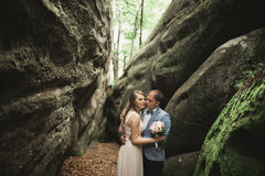 Gorgeous wedding couple kissing and hugging in forest with big rocks Stock Photography