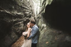 Gorgeous wedding couple kissing and hugging in forest with big rocks Stock Photos