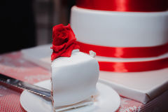 Gorgeous white cake decorated with red flowers, roses, ribbons and bow. Wedding Royalty Free Stock Photo