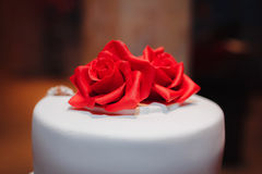 Gorgeous white cake decorated with red flowers, roses, ribbons and bow Stock Photo