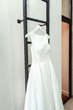 Gorgeous white wedding dress on a fire ladder at the balcony. brides accessories in a wedding day.  Stock Image