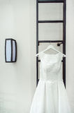 Gorgeous white wedding dress on a fire ladder at the balcony. brides accessories in a wedding day.  Stock Photos