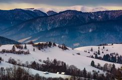 Gorgeous winter landscape in mountainous rural are. Beautiful countryside scenery with village and forest on snow covered rolling hills at sunrise Stock Photo
