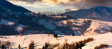 Gorgeous winter landscape in mountainous rural are. Beautiful panoramic countryside scenery with village and forest on snow covered rolling hills at sunrise Royalty Free Stock Photo