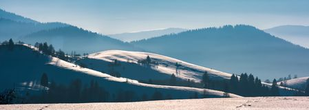 Gorgeous winter panorama of rolling hills. Gorgeous winter panorama of snowy rolling hills. beautiful landscape with forested mountains in a distance Stock Photography