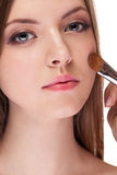 Gorgeous woman applying make up on her face with a brush Stock Photography