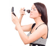 Gorgeous woman applying makeup with brush looking Stock Images