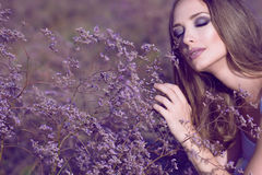 Gorgeous woman with artistic glam make up and long hair touching softly violet flowers with closed eyes enjoying their aroma. On the field. Perfume and Stock Images