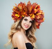 Gorgeous woman in autumn leaves crown. Beautiful model with makeup, clear skin and wavy hairstyle on gray background.  royalty free stock photos