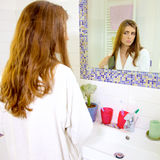 Gorgeous woman with bathrobe brushing hair in bathroom in the morning looking mirror Royalty Free Stock Images