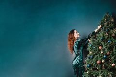 Gorgeous woman in a beautiful dress decorating Christmas tree. Copy space for your text and design. Luxury green, blue, golden. Colors. Home and family warmth stock image