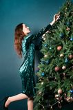 Gorgeous woman in a beautiful dress decorating Christmas tree. New Year concept. Luxury green, blue, golden colors. Home and. Family warmth. Banner for holiday royalty free stock image