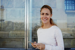 Gorgeous woman with beautiful smile holding smart phone and looking at camera while waiting for someone outdoors, Royalty Free Stock Photo