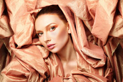 Gorgeous woman beauty wrapped in fabric. Gorgeous woman beauty wrapped in golden fabric Royalty Free Stock Photography