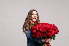 Gorgeous woman with big earings holding roses and smiling.