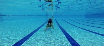 Gorgeous woman in bikini swimming underwater Stock Photos