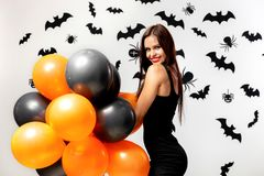 Gorgeous woman in black dress smiles and holds black and orange balloons on a white background with black bats and royalty free stock image