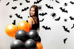 Gorgeous woman in black dress smiles and holds black and orange balloons on a white background with black bats and royalty free stock images