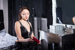 Gorgeous Woman in Black Sitting at her Room. Close up Gorgeous Young Woman in Sexy Elegant Dress Sitting at her Room While Waiting Stock Photo