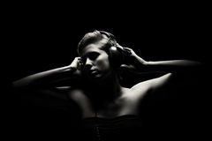 Gorgeous woman in black and white listening to music. Gorgeous woman in black and white tense light listening to music Stock Photography