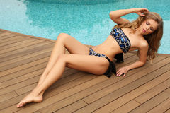 Gorgeous woman with blond curly hair in luxurious swimsuit Royalty Free Stock Image