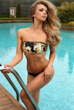 Gorgeous woman with blond curly hair in luxurious swimsuit Stock Photo