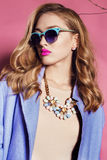 Gorgeous woman with blond curly hair in spring outfit: elegant coat, dress and sunglasses Royalty Free Stock Images