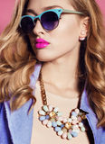 Gorgeous woman with blond curly hair in spring outfit: elegant coat, dress and sunglasses Royalty Free Stock Photos