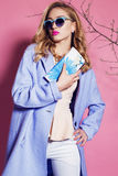 Gorgeous woman with blond curly hair in spring outfit: elegant coat, suit and sunglasses Stock Photography