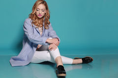 Gorgeous woman with blond curly hair wears elegant casual clothes Royalty Free Stock Photo