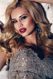 Gorgeous woman with blond hair and bright makeup,wearing luxurious sequin dress. Fashion interior photo of gorgeous woman with blond hair and bright makeup Royalty Free Stock Image