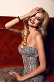Gorgeous woman with blond hair and bright makeup,wearing luxurious sequin dress Royalty Free Stock Image